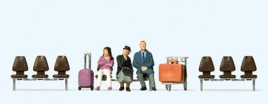 Drei wartende Reisende. mit Koffer