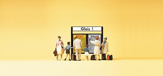 Reisende vor Fahrplantafel
